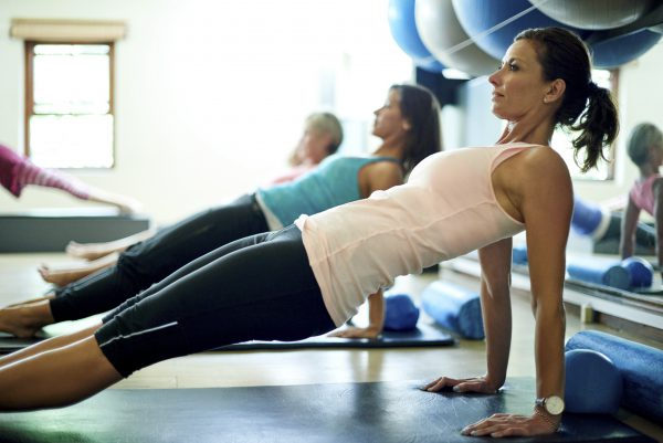 Shot of a group of women working out in a pilates class